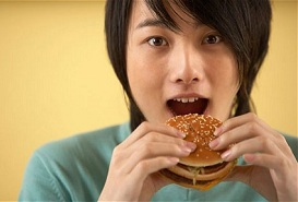 asian woman eating hamburger