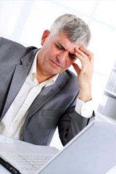 man with headache at computer