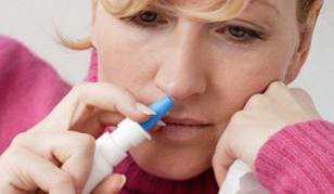 Woman using a nasal decongestant