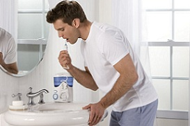man using the Waterpik water flosser