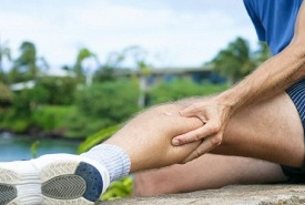 man suffering from calf cramp