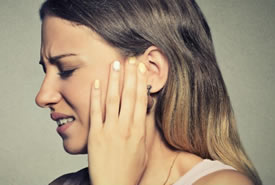 woman suffering from tinnitus